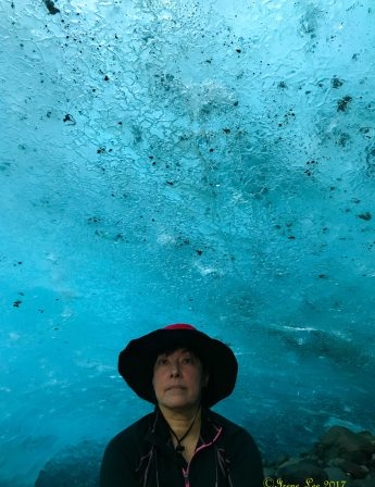 Irene sitting inside an ice cave under Root Glacier