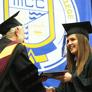 MCC Trustee Diana Osborn hands a diploma to a smiling MCC student on the Walker Arena stage. Both are wearing their Commencement regalia.