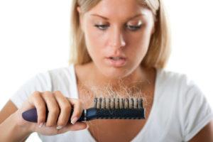 demir eksikliği nedeni ile saçları dökülen kadın elinde tarak