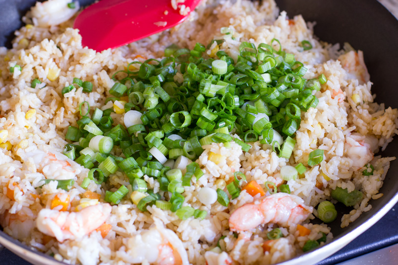 Adding the green onion to the fried rice