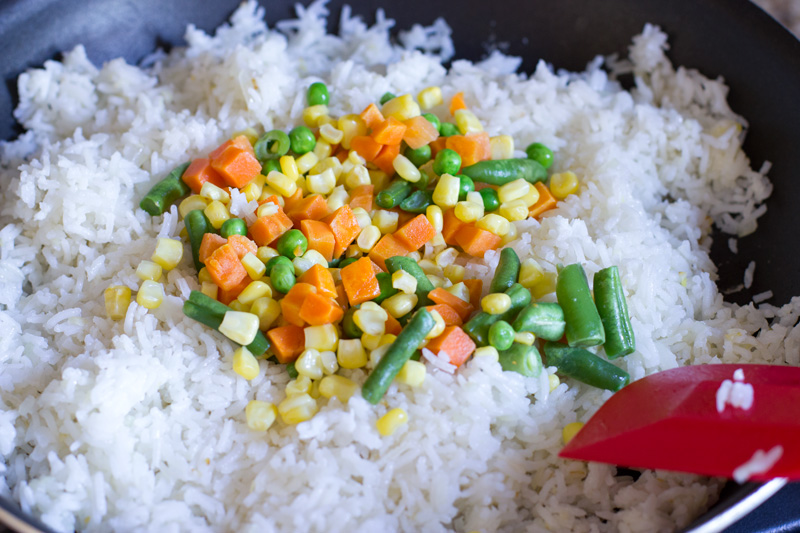 Adding veggies to the fried rice