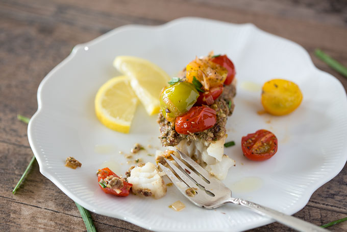 Final image of baked cod with tapenade and warm tomato salad on a plate