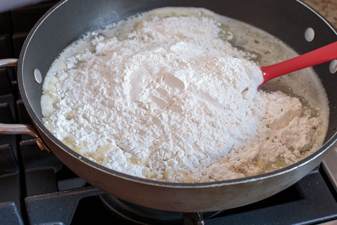 Adding the flour to the hot broth in the pan