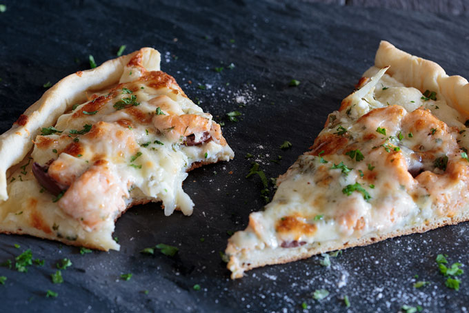 Two slices of salmon and herb pizza, one missing bites
