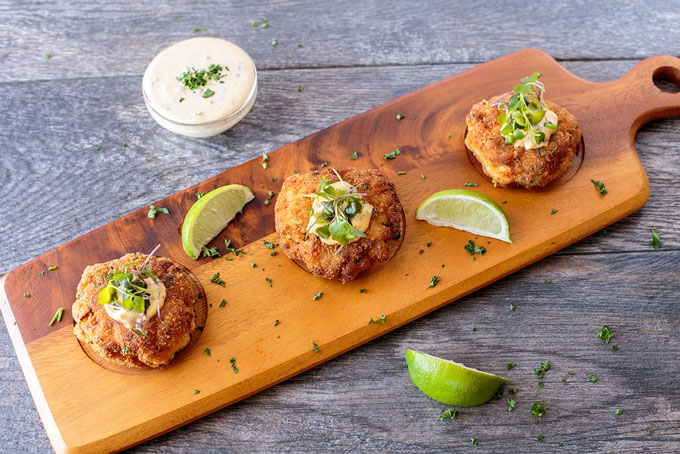 Fish cakes on a serving board with remoulade and lime wedges