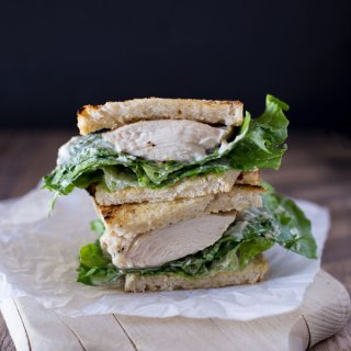 Stacked halves of the prepared grilled chicken Caesar sandwich portrait orientation