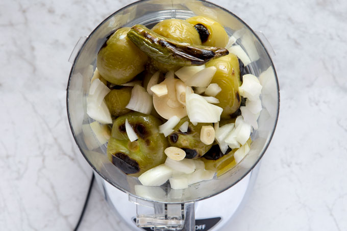 Roasted tomatillos and serrano in the food processor with onion and garlic