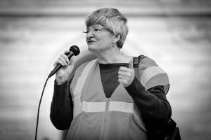Photo of Karen speaking into a microphone at a rally in 2017