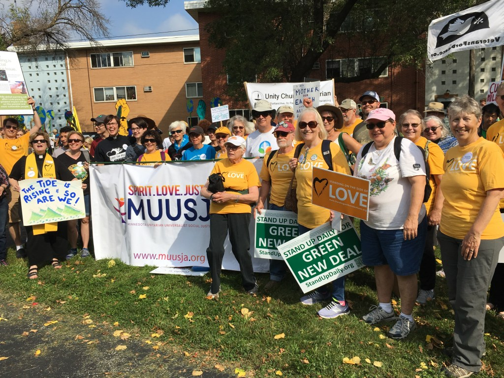 UU's in yellow Stand With Love t-shirts gathered at Saint Paul Climate Strike with MUUSJA banner on 9-20-2019