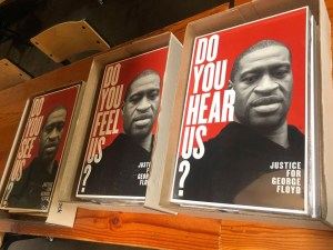 posters on a table with image of George Floyd, text says Do you see us?, Do you feel us?, Do you hear us?