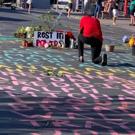 a man kneels praying at a street shrine saying Rest in Power atop the names of people killed by police, painted on the street