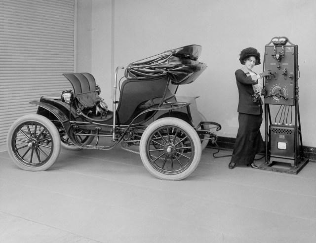 cca. 1912 - O femeie folosește un încărcător manual pentru a încărca bateriile unei mașini Columbia Mark 68 Victoria. Pope Manufacturing Company a produs acest model în 1906