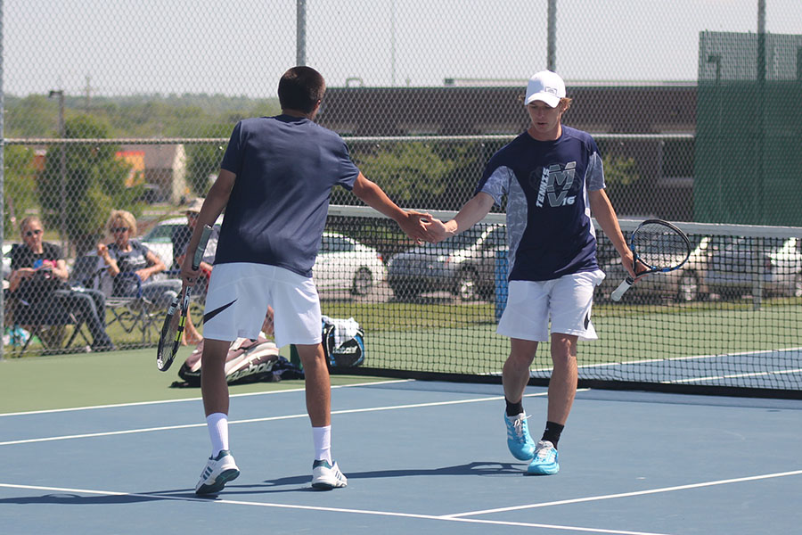 Senior Alec Bergeron high fives his doubles partner after scoring a point.