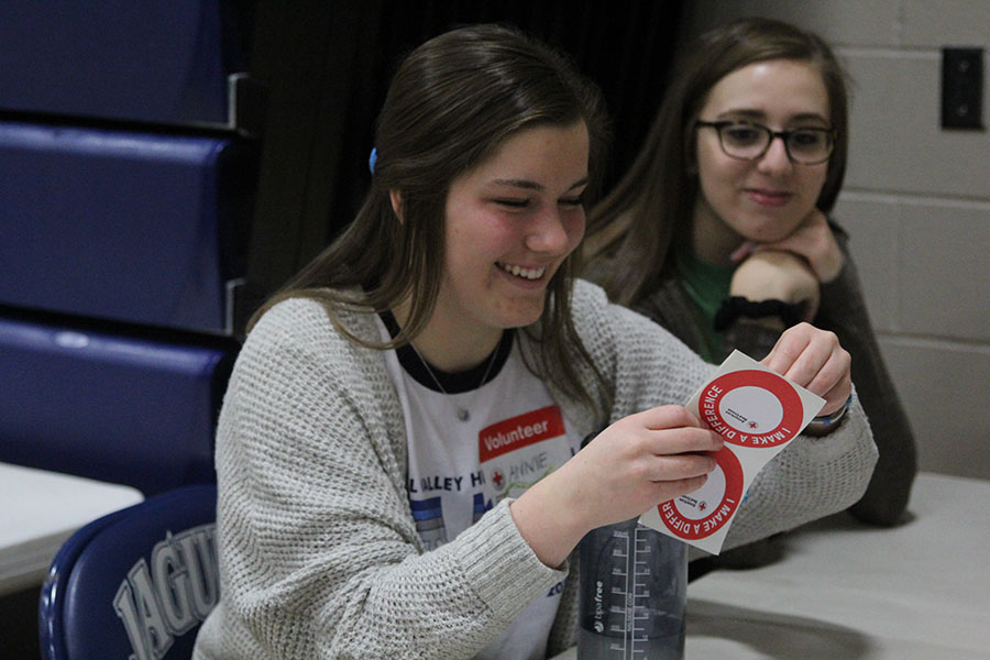 By Abby Doughty With a big smile on her face junior Annie Myers passes out stickers to blood donors alongside senior Claire Boone