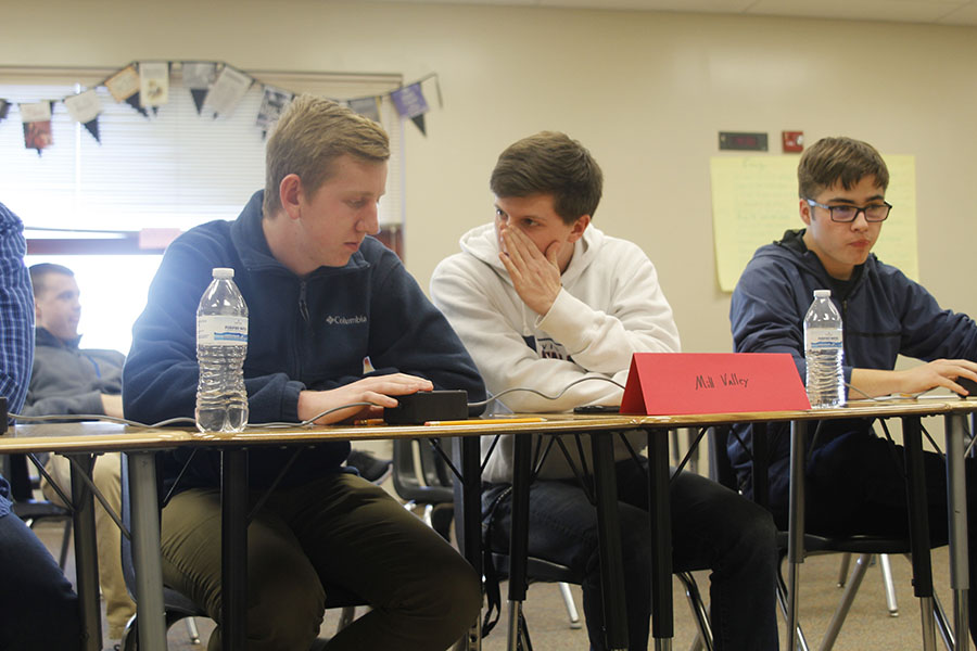 Discussing+the+answer+to+a+question%2C+senior+Sam+Phipps+whispers+to+teammate+senior+Landon+Butler+during+the+first+round+of+the+regional+tournament+on+Thursday%2C+Feb.+1.