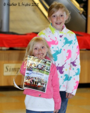 Reagan (L) and her sister Cadence with their photo and souvenir eyewear from leading jockey Dean Butler