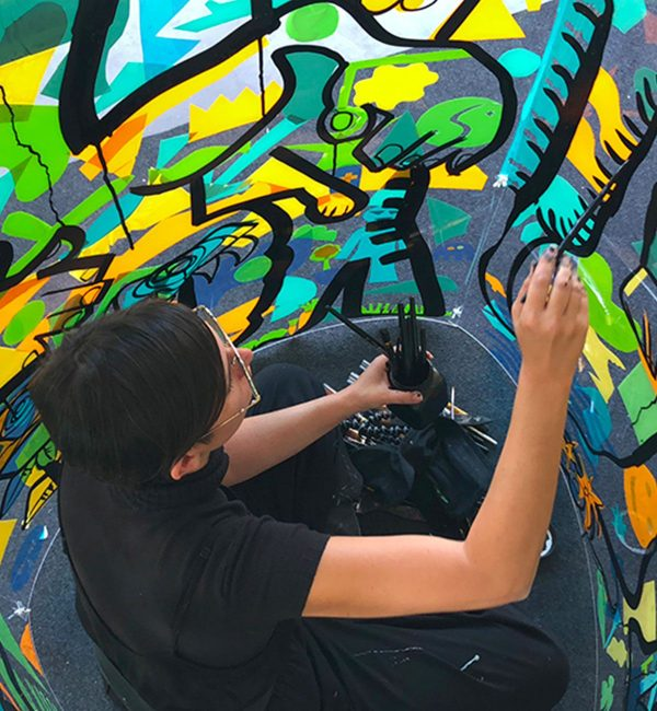 une femme peint à l'intérieur d'un cylindre géant lors d'une animation fresque géante