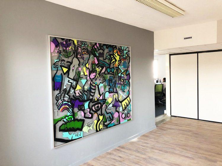 un tableau géant coloré et en plexi transparent, encadré dans une entreprise sur un mur gris