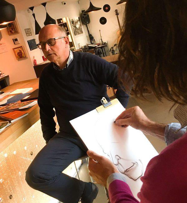 un artiste aux cheveux longs et veste fuchsia en train de réaliser la caricature noir et blanc format A3 en face de son modèle homme assis en face de lui en animation caricature papier à Lyon