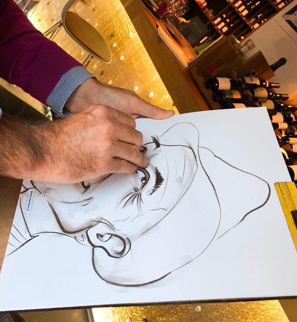 Gros plan sur un dessin caricature noir et blanc format A3 avec les mains du caricaturiste Christophe Chazot en train de dessiner à Lyon en animation Close up