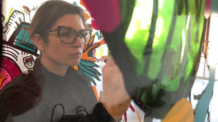 l'artiste aNa en action dans son tube transparent pour fresque géante serious play