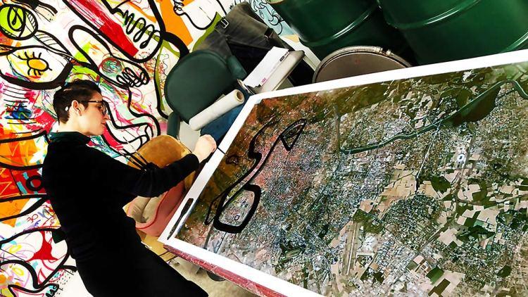 l'artiste aNa dans son atelier de Lyon penchée sur sa table en train de peindre une fresque sur plexi à partir du plan google earth imprimé de la Ville de Lyon métropole
