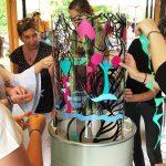Un groupe d'employés de la Région Auvergne Rhône Alpes en séminaire de stimulation du lien social et cohésion en train de mettre en couleurs une fresque Totem box My Art Box au Parc des Oiseaux lors d'un team building autour des enjeux de développement du territoire