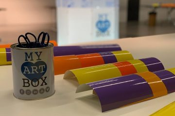 matériel du protocole artistique d'atelier team building myartbox composé d'un pot contenant des ciseaux de découpage, des adhésifs de couleurs posés sur une table, et dans le fond le support lumineux de fresque plexi lumineuse de l'artiste aNa