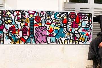 aNa artiste devant une œuvre collective encadrée peinte lors d'un team Building Tours