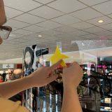 Une personne colle une étoile jaune sur un tube plexi géant en animation fresque adhésive Totem Box