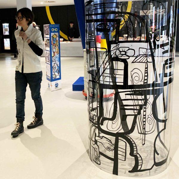 L'artiste et son Tube plexi géant pré dessiné lors d'une animation fresque aNa Artiste