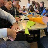 Des personnes assises autour d'une grande table lors d'un coaching programme cohésion en animation fresque à Rouen format Totem Box XL My Art Box