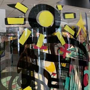 Un symbole de soleil jaune découpé dans du vinyle de couleur et posé sur le Tube plexi Totem Box Animation Fresque My Art Box
