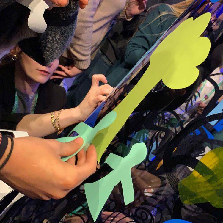 Les participantes à une animation Fresque en train de poser des personnages verts découpés sur un arbre jaune déjà collé sur le Tube plexi Totem Box XL my art box lors d'une animation team building créative fresque stickers