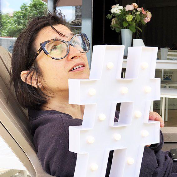 aNa artiste pose derrière un Hashtag lumineux blanc pour présenter son service de puzzle décoratif qui aide à développer son business avec instagram