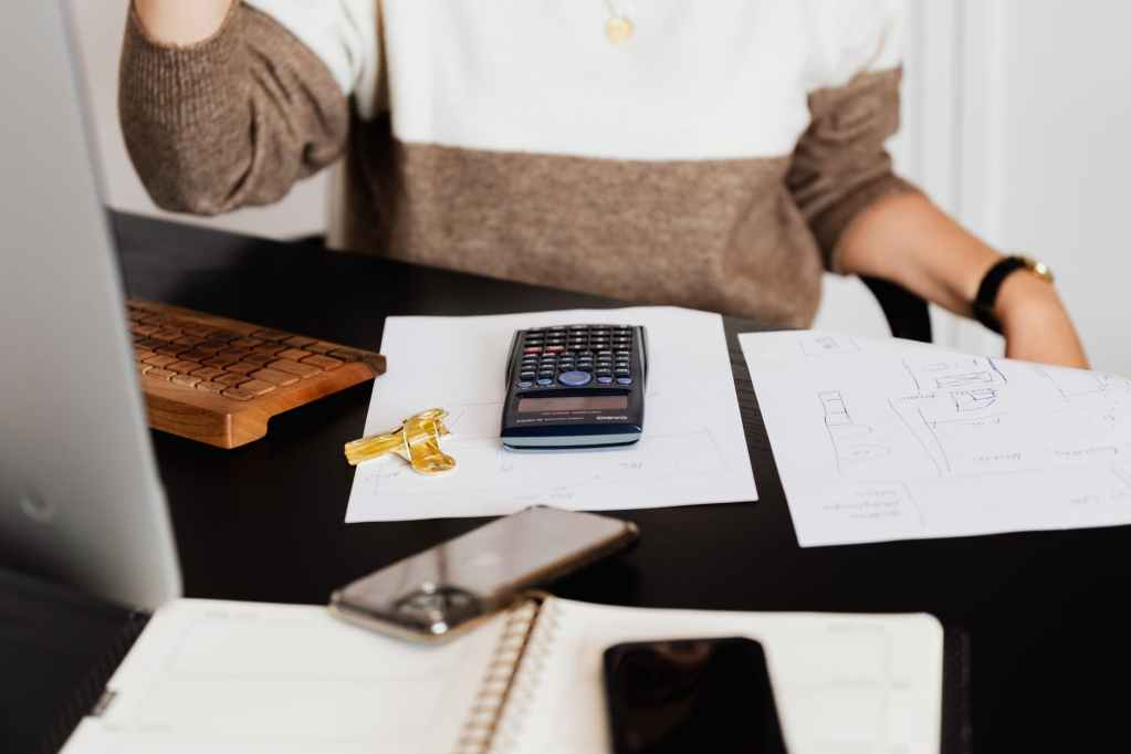 Woman using calculator how to pay your high energy bill