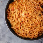 jollof spaghetti and prawns in a black pan.