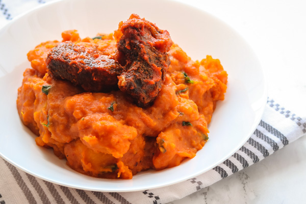 yam porridge and peppered beef served in a white bowl.