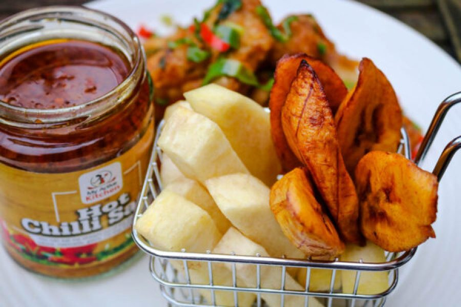 overhead shot of fried yam and plantain with a side of hot chilli sauce on a white plate
