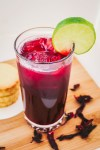 an angled overhead shot of zobo drink garnished with a slice of lime, beside it are stack of cookies