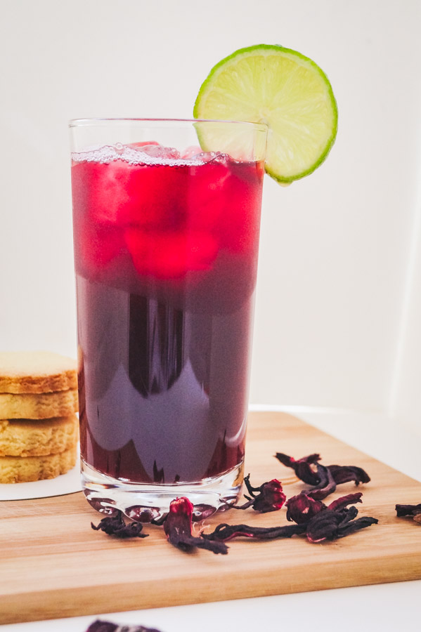 a tall image of hibiscus drink with a garnish of lime rind