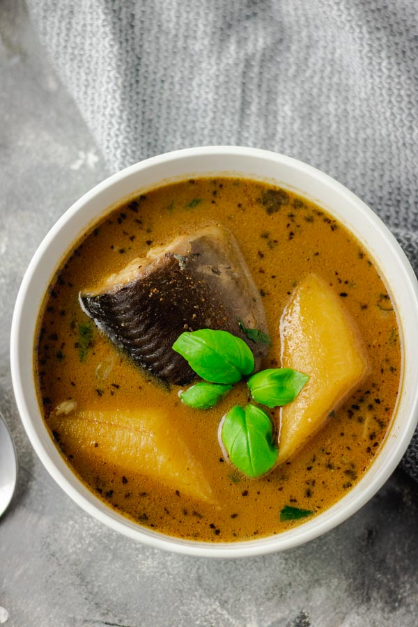 catfish pepper soup with plantain in a white bowl.