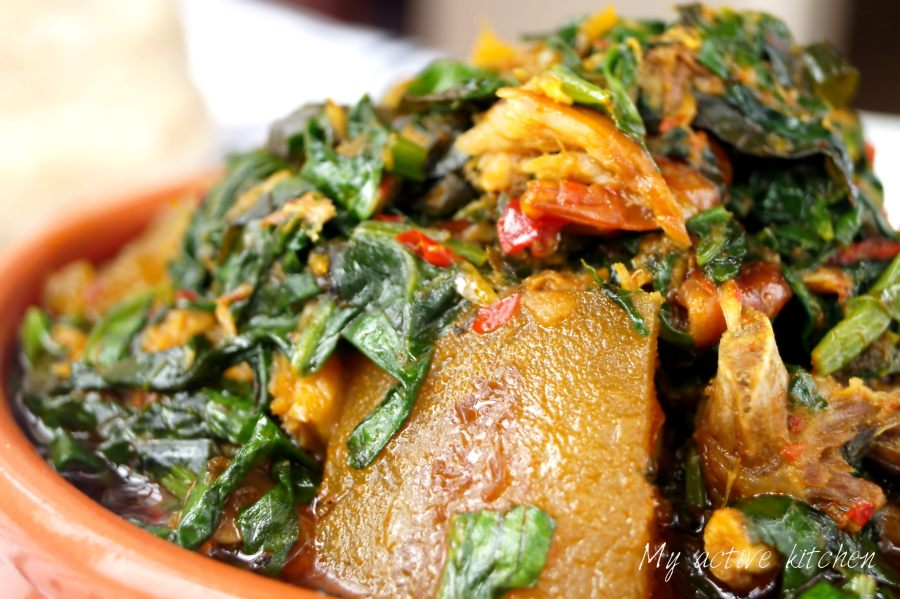 A close shot of efo riro (spinach stew) in a brown ceramic bowl