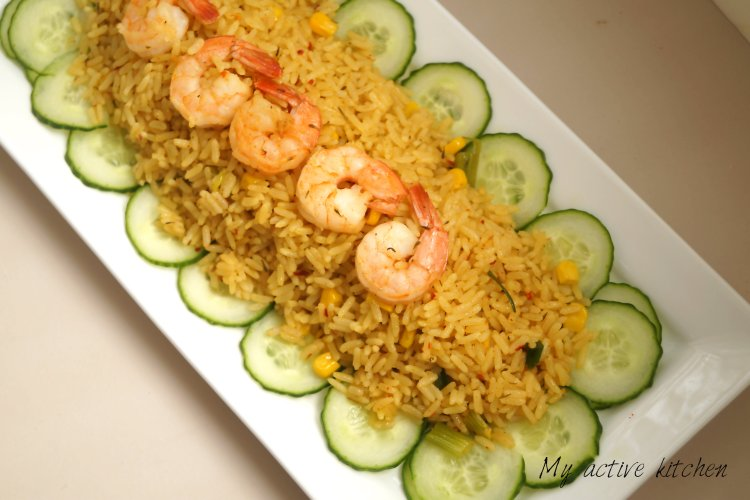 overhead shot of rice and shrimps served on a rectangular white plates.