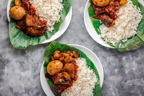 3 plates of ofada stew and plain rice served in a leave placed on white plates.