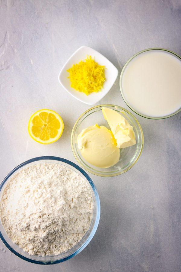 ingredients in bowls, it includes flour, butter,lemon, milk and lemon zest.