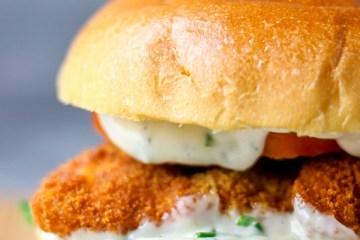 Close shot of crispy fish burger with mayo dressing