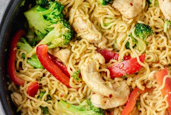 cropped overhead shot of chicken ramen noodle stir fry in a skillet made with broccoli and bell pepper and stir fry sauce.