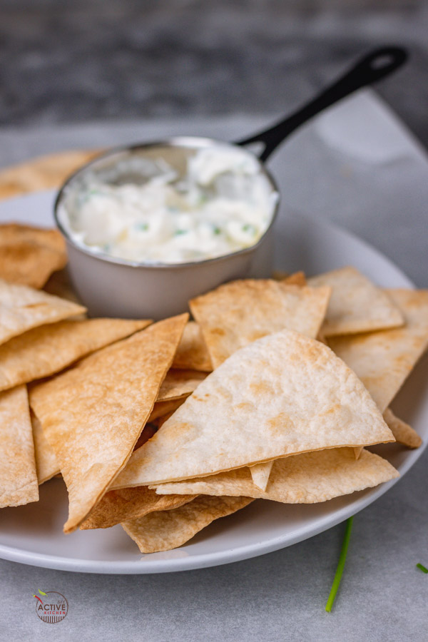 baked flour tortilla chips in a bowl with a side of sour cream and chives dip.