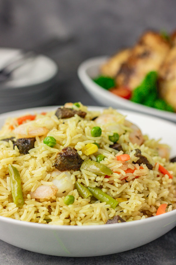 Nigerian fried rice served with a side of chicken thighs.